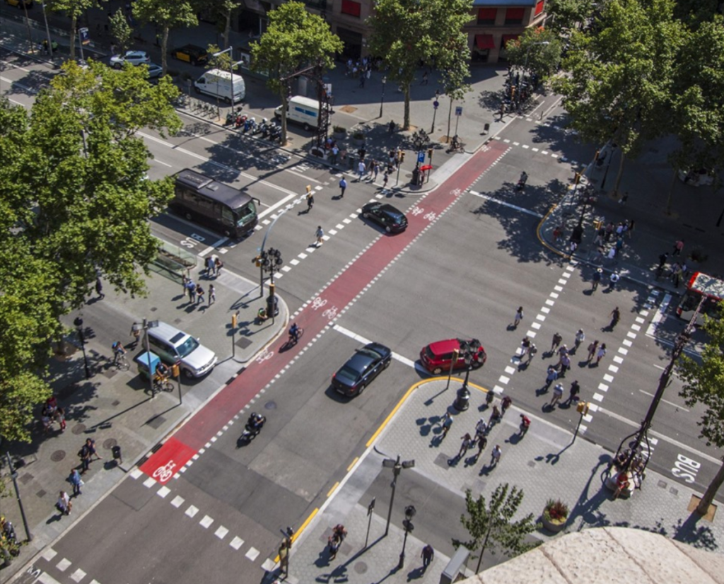 A rendering of an urban intersection where pedestrians, bicycles, public transit, and automobiles all use the road.